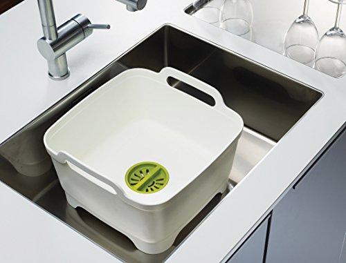 Egouttoir à vaisselle en plastique robuste, blanc et vert, avec système d'évacuation de l'eau de rinçage et poignées latérales. Il se pose dans ou à côté de l'évier. Joseph Joseph